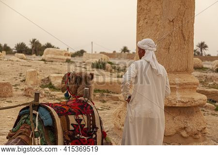Palmyra, Syria 04-02-2010: A Local Arabic Tour Guide Is Standing By His Dromedary Camel By The Ancie