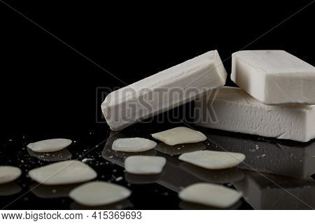 White Bars Of Soap Are Stacked On Top Of Each Other With Leftover Soap Slieves And Pieces Lying Arou