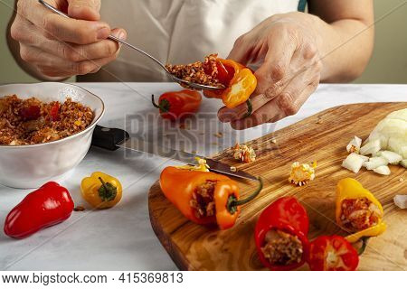 A Woman Chef Is Stuffing Peppers Using A Metal Spoon. She Has Rice Filling With Onions, Ground Meat,