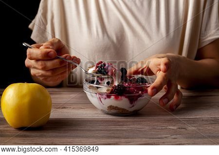 Woman Is Eating A Fresh Home Made Glass Bowl Of Creamy Yogurt Parfait With Berries, Muesli And Seeds