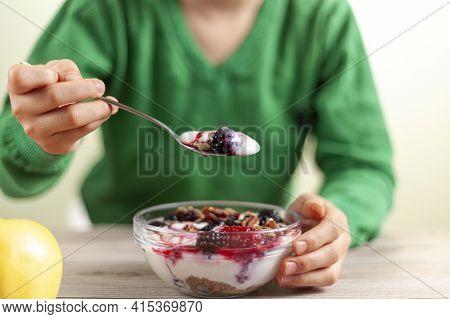 A Kid With Green Shirt Is Eating Fresh Homemade Glass Bowl Of Creamy Yogurt Parfait With Berries, Mu