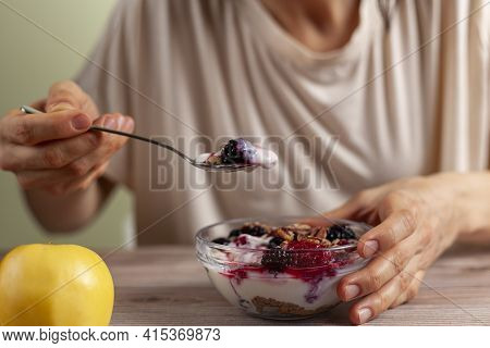A Caucasian Woman Is Eating A Fresh Home Made Glass Bowl Of Creamy Yogurt Parfait With Berries, Mues