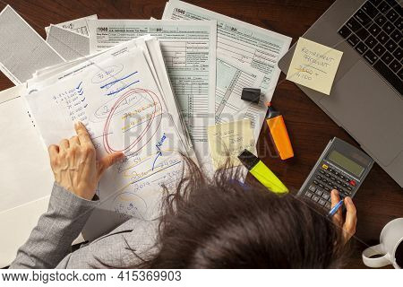 A Woman Is Preparing Her Tax Return In Her Office Using Forms Calculator Laptop And Various Notes As