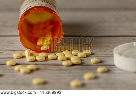 An Orange Prescription Medication Bottle Tipped Over On Wooden Table With Round Yellow Pills Scatter
