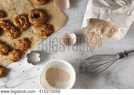 Flat Lay Image Of  Fresh Handmade Pastry Cooling On Baking Paper With Seeds Scattered On Marble Kitc