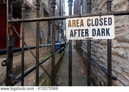 Area Closed After Dark Sign On Metal Plate Is Attached To The Metal Railings Of A Door In Front Of A