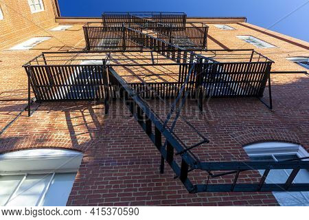 Bug Eye View Of Vintage Black Metal Construction Fire Escape Ladder With Makeshift Balconies And Acc