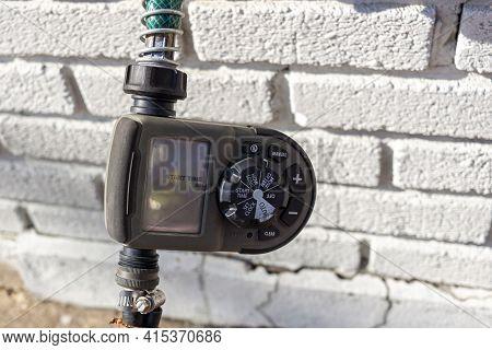 Alexandria, Va, Usa 11-28-2020: Close Up Digital Hose Timer Attached To Garden Hose Coming Out Of A