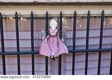 A Cute Straw Fabric Blonde Girl Doll Wearing Pink Vintage Folk Dress Is Attached On The Window Guard