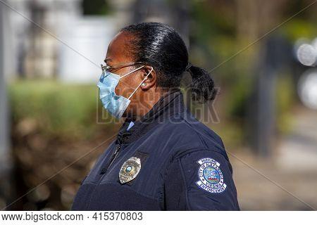 Alexandria, Va, Usa 11-28-2020: An African American Police Officer Working In Parking Enforcement De