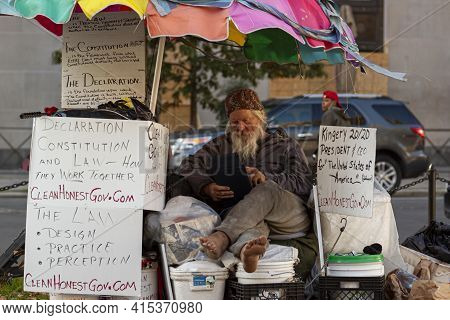 Washington Dc, Usa 11/06/2020: An Elderly Homeless Caucasian Man Is Sitting At A Stand Surrounded By
