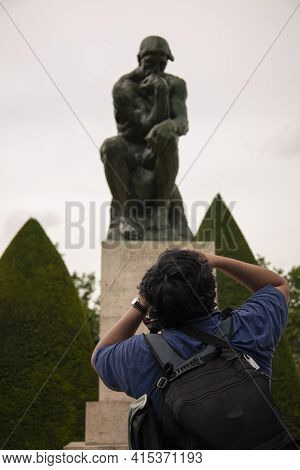 Paris, France 06/12/2010: A Photographer With A Backpack Is Taking A Close Up Photo Of The Famous Th