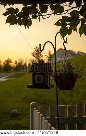An Abstract Concept Image Taken At Sunset Showing A Stand Alone Metal Hanger Rack With A Bird House