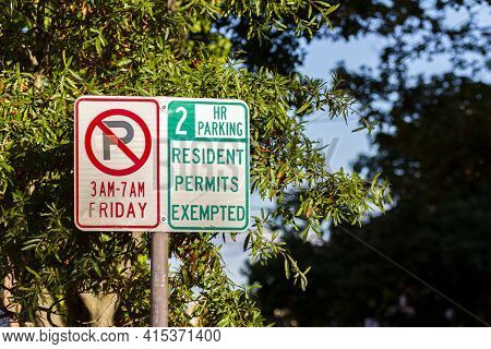 Side By Side Traffic Signs One Showing No Parking On Friday And The Other Showing 2 Hours Maximum Pa