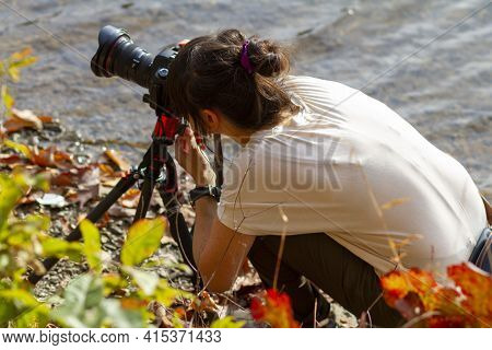 A Young Caucasian Woman Wearing Casual Clothes Is Kneeling On The Ground By A River. She Is Trying T