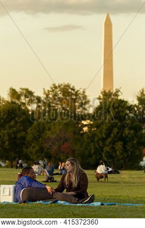 Washington Dc, Usa 10/02/2020: An Interracial Couple Is Sitting On A Picnic Blanket On Gravelly Poin