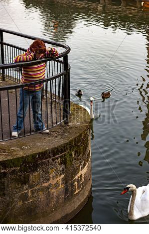 Bath, Uk 03/06/2010: A School Aged Caucasian Girl With Red Hair Wearing Colorful Sweater And Jeans I