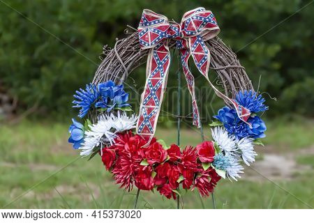 A Wreath Of Blue, White And Red Flowers With Confederate Flag Themed Ribbons. This Wreath Was Placed