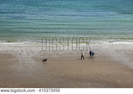 Isle Of Wight, Uk 04/25/2010: Aerial View Of Three Elderly People Strolling On A Sandy Beach In The