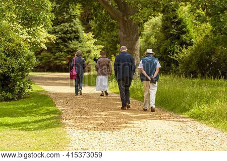 Two Well Dressed Elderly Men And Two Elderly Women Are Having A Leisurely Stroll In A Park. They Wal