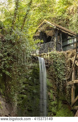 Long Exposure Image Of A Small Waterfall. There Is A Wooden House On Top Of The Cliff At The Edge Of