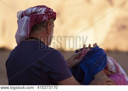 Close Up Image Of An Elderly Caucasian Couple Visiting Wadi Rum.the Tourists Are Wearing The Traditi