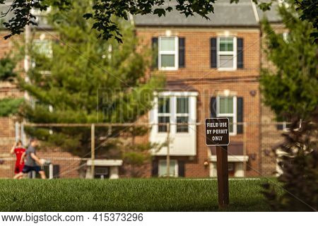 A Selective Focus Image Of A Wooden Sign Post On A Field That Says