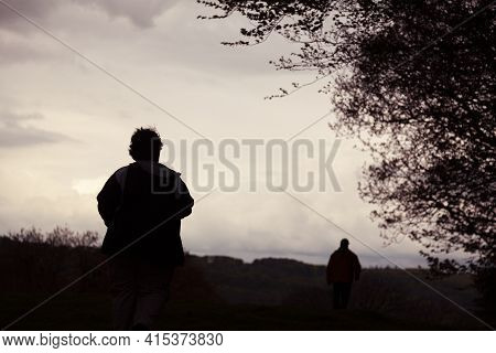 Silhouette Of Two Men Walking Away In A Rural Area At Sunset On A Cloudy Day. The Man Behind Is In F