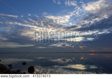 An Abstract Image Taken At A Lakefront At Sunset. Image Shows A Spectacular Cloudy Sky And Its Refle