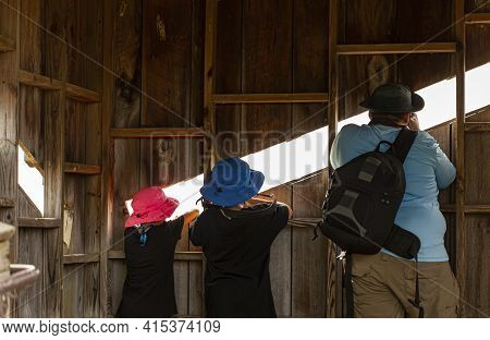 A Man, His Two Kids Are In A Wooden Hide At A Wildlife Refuge Trying To Take Wildlife Images Through