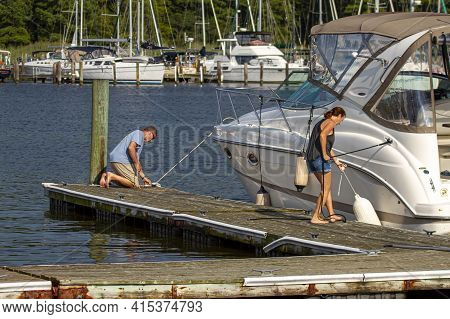 Stensville, Md 08/18/2020: A Caucasian Couple Is Docking Their Cabin Cruiser Boat To The Port By Tyi