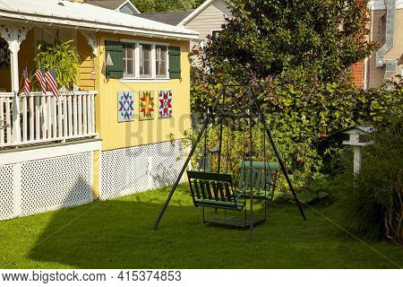 Chesapeake City, Md, Usa 08/25/2020: A Green, Metal Vintage Garden Swing On The Front Yard Of A Trad