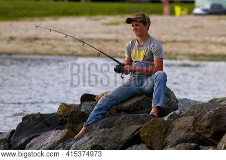 Rock Hall, Md 08/22/2020: A Boy Is On The Rocks, With A Fishing Rod Trying To Catch Fish From Chesap
