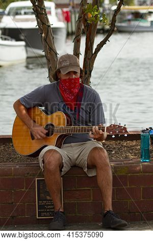 Annapolis, Md 08/21/2020: A Young Caucasian Man Is Sitting On A Brick Wall In Annapolis Marina And P
