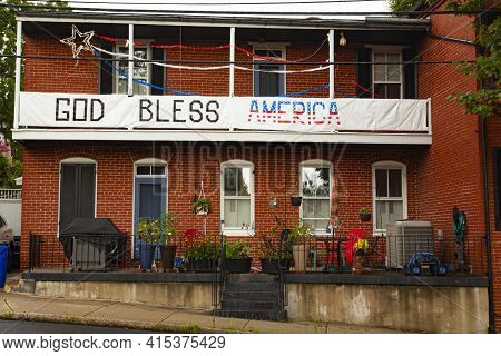 Frederick, Md, Usa 08/14/2020: An Old Two Story House With Clutters Of Toys And Potted Plants On The