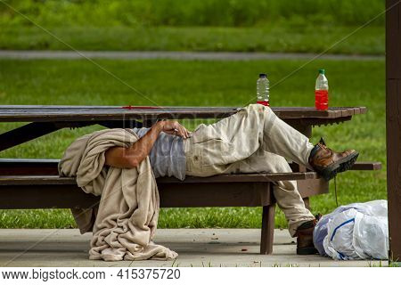 A Homeless Caucasian Man Is Sleeping On A Picnic Table In A Shaded Area Of A Park. He Is Covering Hi