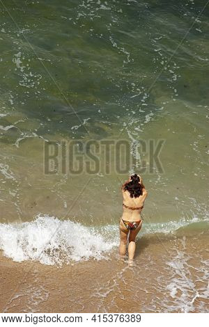 Aerial Image Featuring A Young Caucasian Girl In Bikini Swimsuit With Her Hands On Head Hesitating T