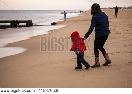 A Small Kid Wearing Red Winter Coat, Jeans And Boots Is Trying To Run To The Sea In The Beach. Hyper