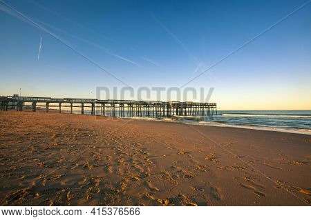 Isolated Image Of A Fishing Pier At Sunset Or Sunrise. Image Features The Wooden Pier With Lamp Post
