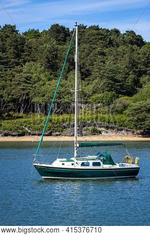 Isolated Image Of A Small Sail Boat That Is Anchored On A Bay Close To The Coast. There Is Nobody On