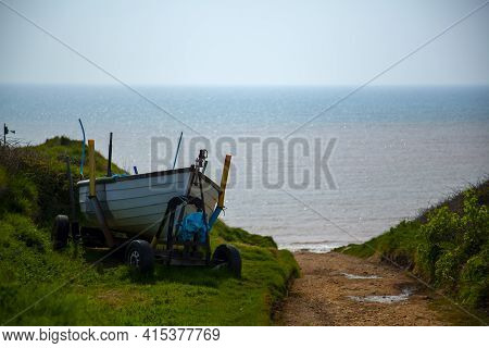 A Small Wooden Boat Is Left On A Towing Wagon By A Dirt Path Near The Ocean. The Road Leads To A Sma