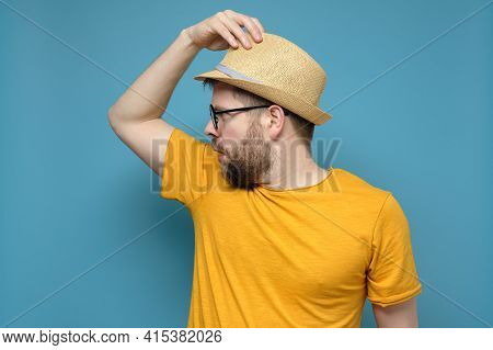 Strange, Confused Man In A Straw Hat Makes A Greeting Gesture And Surprise Looks Away. Blue Backgrou