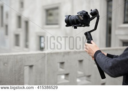 Filmmaking, Hobby And Creativity Concept - Modern Dslr Camera On 3-axis Gimbal In Male Hands Over Co
