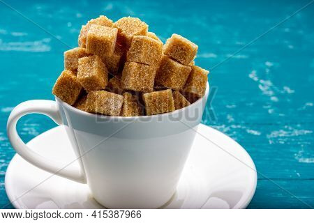 A Cup Full Of Cane Sugar. A Slide Of Sugar In A White Cup. Granular Sugar Cubes