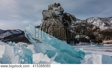 The Rock Of An Unusual Shape Rises Above The Frozen Lake, Against The Background Of Blue Sky And Mou