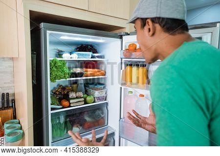 Man Open Fridge Door And Confuse Looking Something To Eat