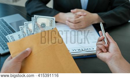 Businessman Hand Offer Bribes Money In Envelope For Signing In A Contract Of Business Project, Gover