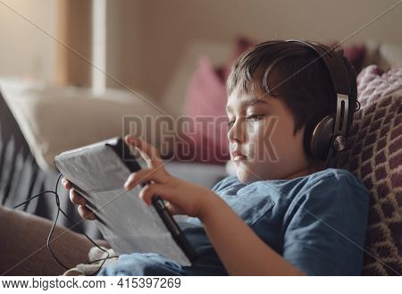 Authentic Portrait Kid Sitting On Sofa Watching Cartoons On Tablet,yong Boy Playing Game On Touch Pa