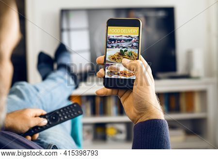 Man Order Food With Mobile App. Close Up Of Man Hand Holding Mobile Phone With Food Order App. Mobil