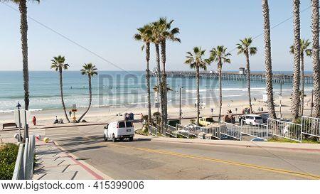Oceanside, California Usa - 8 Feb 2020: Bicyclist Man On Road, People Walking Waterfront Promenade.
